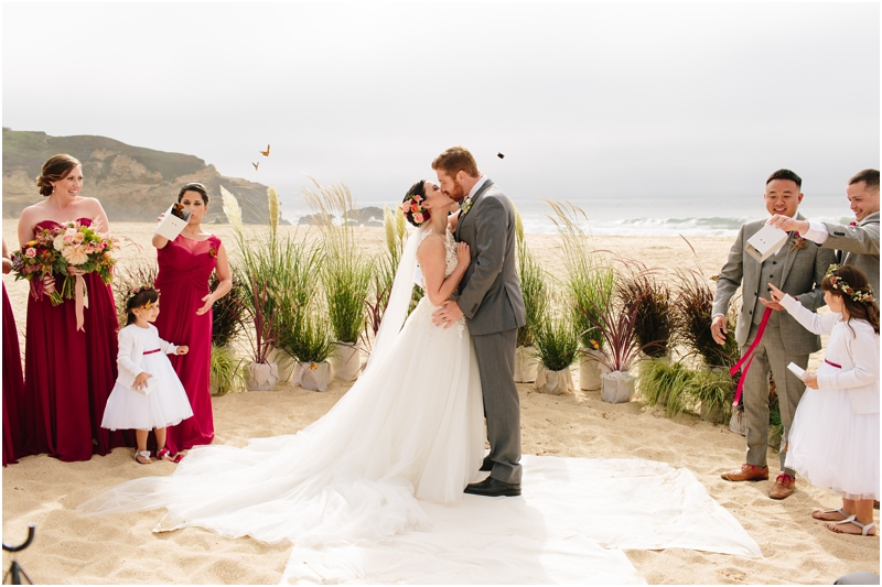 Bride and groom kiss during their wedding ceremony on the beach in Half Moon Bay outside of Half Moon Bay wedding venue La Costanera