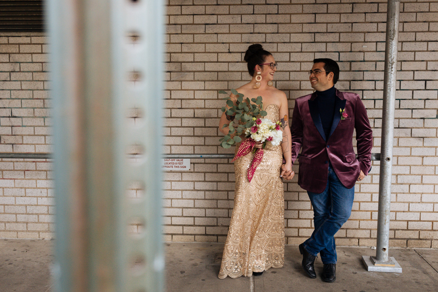 Hip bride and groom stand in an urban area of New York City after their East Village elopement