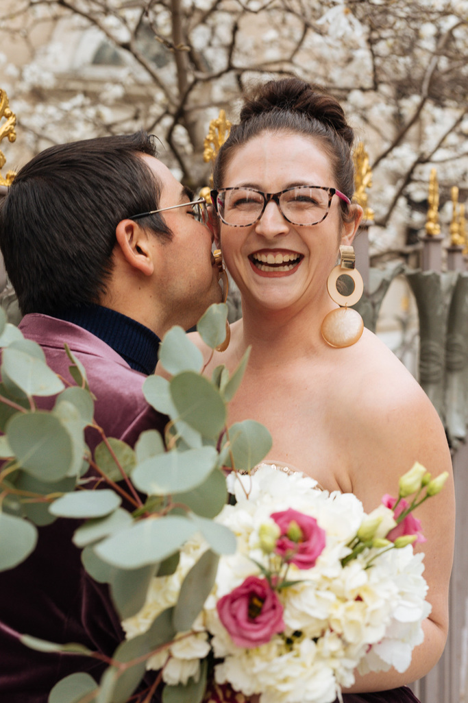Groom whispers something in bride's ear during their East Village elopement in NYC