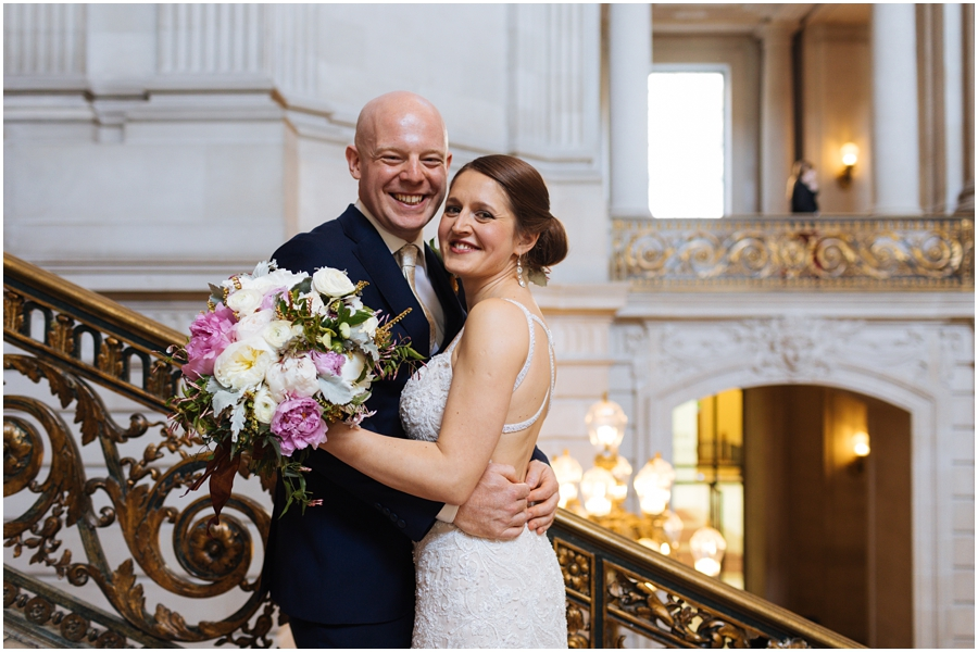 Couple smiles on the Grand Staircase during their San Francisco City Hall wedding in California