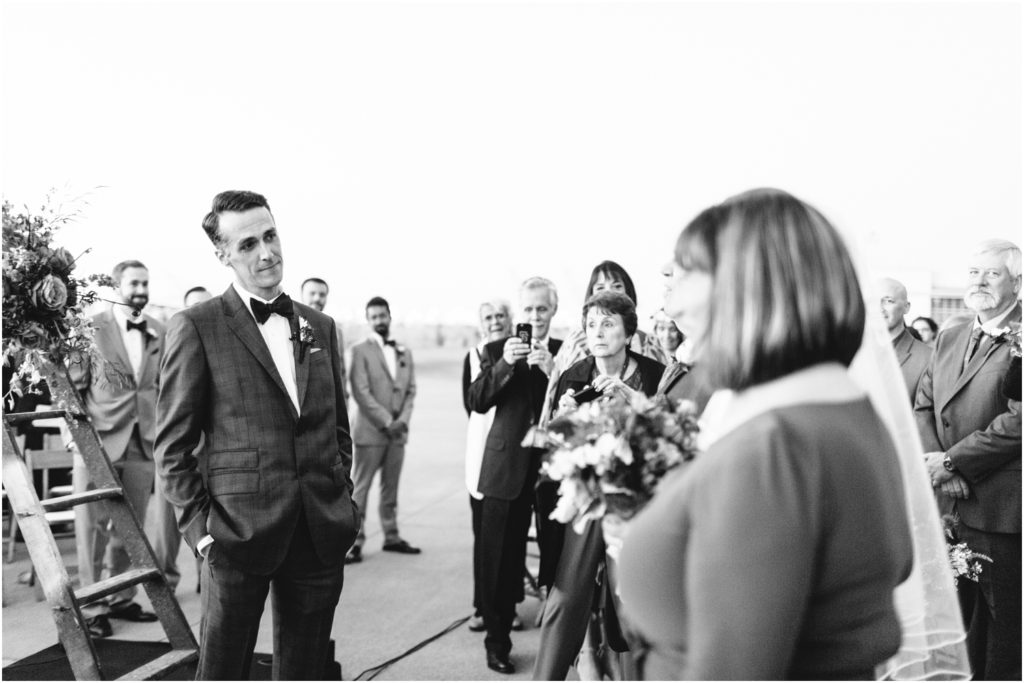 Groom looks at bride as she walks down the aisle - Should We Have a First Look?