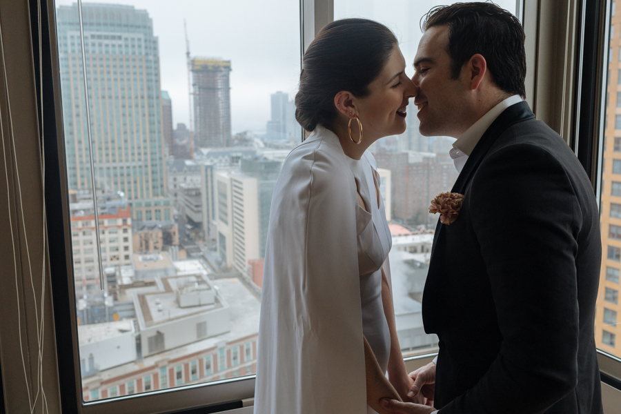 Bride and groom kiss in their apartment before their Brooklyn elopement