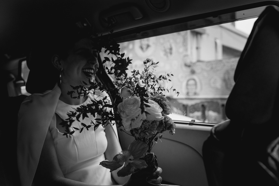 Bride holds her bouquet on her lap in the car on her way to her Brooklyn elopement